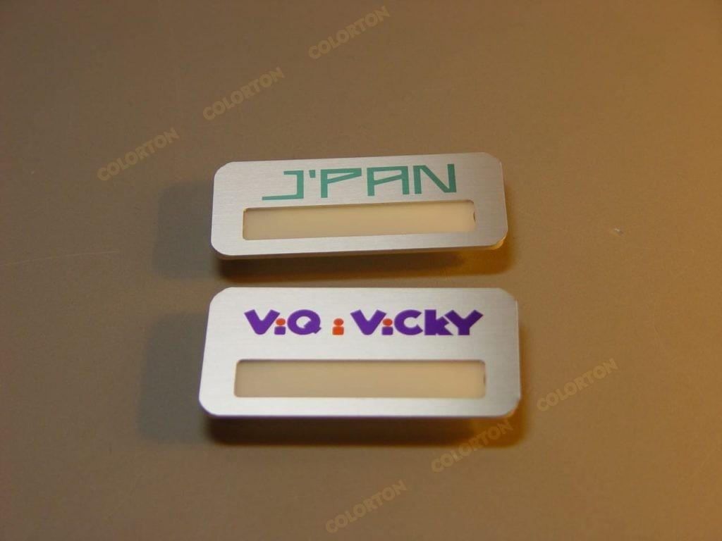 Изображение двух металлических бейджиков с окошком Jpan и Viqivicky